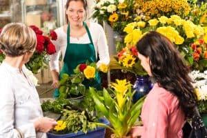 Florist woman preparing bouquet customers flower shop market happy