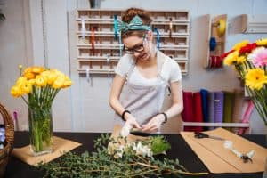 Smiling attractive young woman florist in glasses standing and making bouquet in flower shop